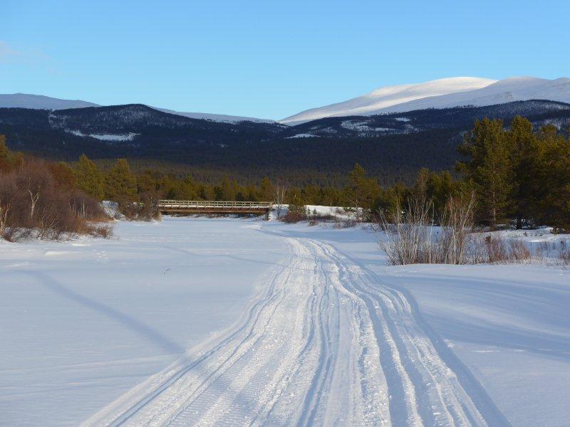 Loipe entlang des zugefrorenen Flussbetts der Folla
